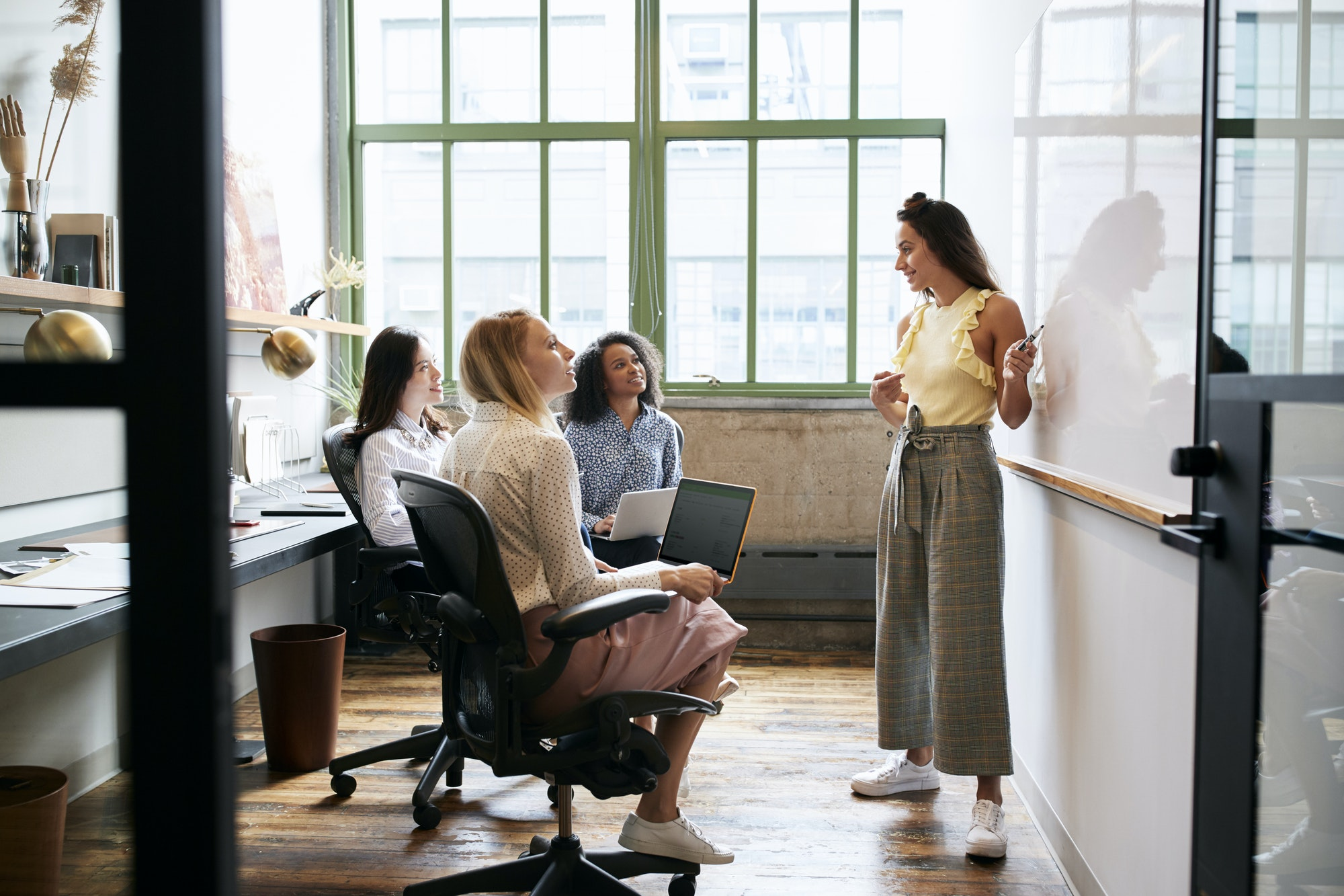 Woman standing at whiteboard in a meeting with female team